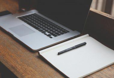 Notebook z wynajmu notebooków. Obok notebooka leży notes i długopis